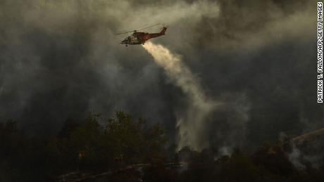Firefighters watched as a Los Angeles Fire Agency helicopter made a drip Saturday at the Palisades Fire in Topanga State Park.