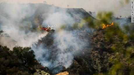 A firefighting helicopter drops water on a brush fire scorching of an area west of Los Angeles Saturday, May 15, 2021.