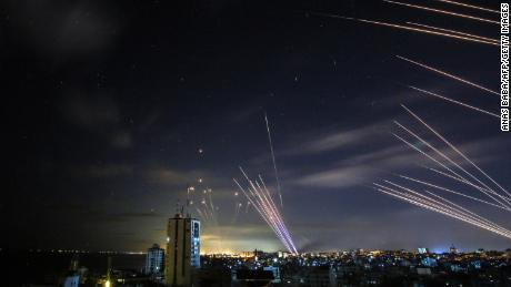 In the background, the Israeli Iron Dome missile defense system intercepts rockets fired by Hamas toward southern Israel from Beit Lahia, in northern Gaza, on May 16.