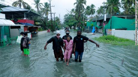Police and rescue personnel evacuate a local resident through a flooded street in a coastal area in Kochi on May 14.