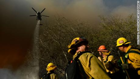 Firefighters keep a lookout as a Los Angeles Fire Department helicopter makes a water drop on the Palisades fire in Topanga State Park, North West of Los Angeles on May 15, 2021.