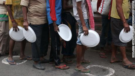 Underprivileged people wait to receive free food  at front in Kolkata, India, on August 27, 2020.