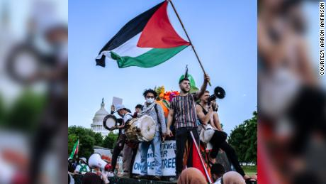 A protester raises a Palestinian flag while riding on a tank-shaped float pushed by marchers along Pennsylvania Avenue, on the west side of the Capitol, on May 15.