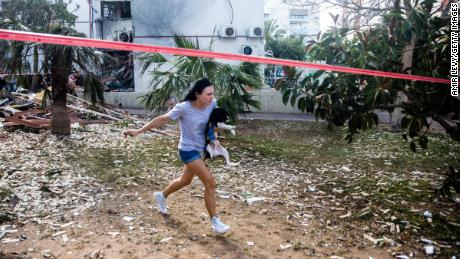 A woman runs for a shelter in Ashdod, Israel, after sirens warned of rockets fired from Gaza on Monday.