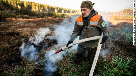 A local activist extinguishes a fire in the village of Shipunovo, Siberia.