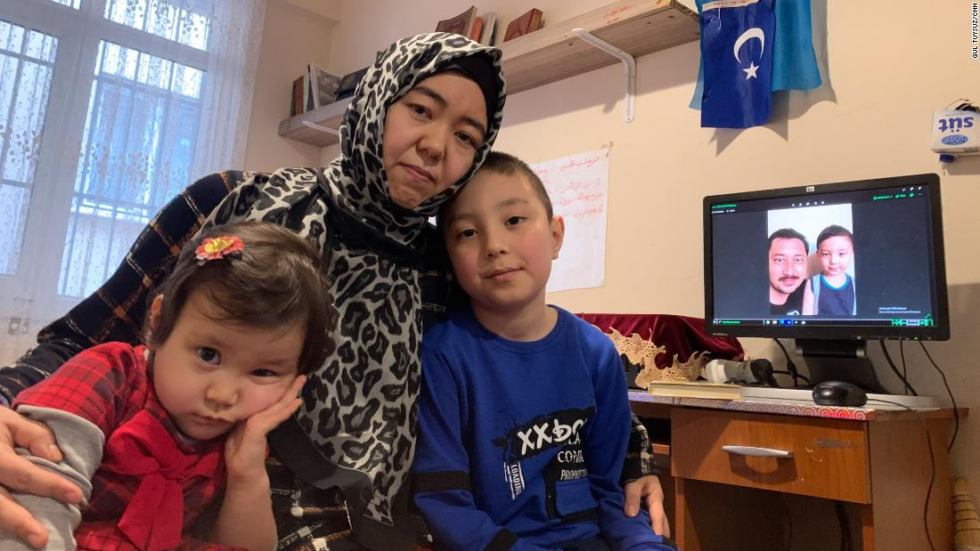 Amannisa Abdullah with daughter, Amina, 3, left, and son Musa, 8. Amina was born in Turkey and has never met her father, Ahmad Talip, pictured on screen in the background with Musa.