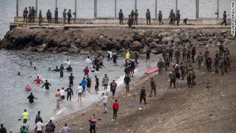 Migrants swam around rocky breakwaters jutting out into the Mediterranean that mark the frontier.