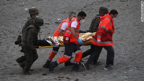L'armée espagnole et le personnel d'urgence emmènent un homme sur une civière.