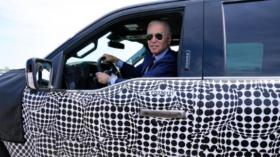President Joe Biden stops to talk to the media as he drives a Ford F-150 Lightning truck at Ford Dearborn Development Center, Tuesday, May 18, 2021, in Dearborn, Mich.