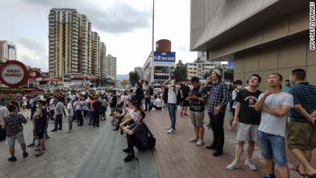 Gli acquirenti guardano SEG Plaza a Shenzhen dopo essere stati evacuati da un edificio traballante.