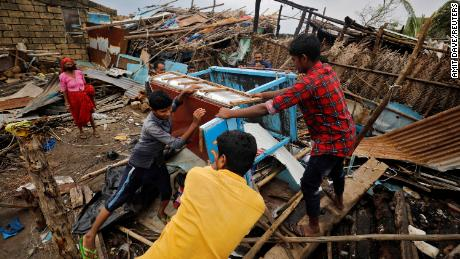 People salvage their belongings from a damaged house after cyclone Tauktae hit in the western state of Gujarat, India.