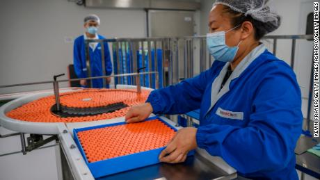 A worker handles vials on the production line at Sinovac Biotech in Beijing, China.