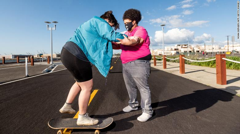 Andy Duran (R) helps Bella Bond learn to skate during the first Chub Rollz event.