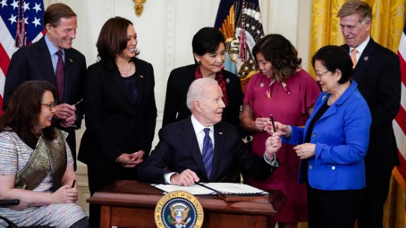 Biden hands out a pen to Sen. Mazie Hirono, D-Hawaii, after signing the COVID-19 Hate Crimes Act on May 20. (AP Photo/Evan Vucci)