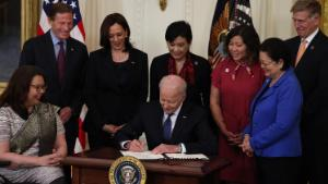 U.S. President Joe Biden signs the COVID-19 Hate Crimes Act into law, as (L-R) Sen. Tammy Duckworth (D-IL), Sen. Richard Blumenthal (D-CT), Vice President Kamala Harris, Rep. Judy Chu (D-CA), Rep. Grace Meng (D-NY), Sen. Mazie Hirono (D-HI) and Rep. Don Beyer (D-VA) look on in the East Room of the White House on May 20, 2021 in Washington, DC.