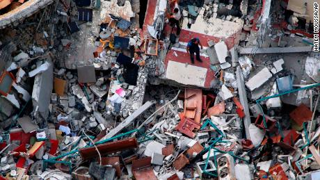 パレスチナ人は、先週初め、イスラエルの空襲にあいましょう市にあるメディアオフィスがあった建物を調査しています。