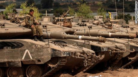 イスラエルの兵士が休戦協定に続き、金曜日ガザ地区との国境近くのステージでタンクの上に座っている。
