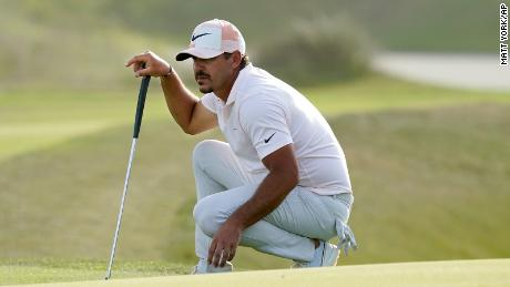 Koepka lines up a putt on the 16th green during the third round.