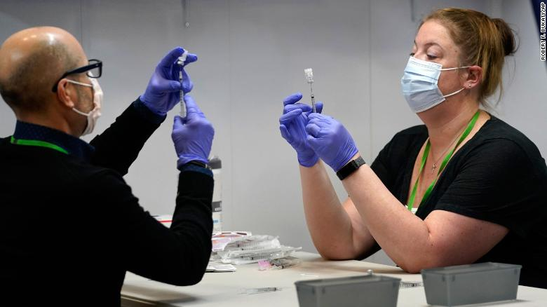 Pharmacy technicians fill syringes with Pfizer's Covid-19 vaccine March 2 at the Portland Expo in Portland, Maine.