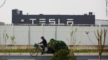 A man riding a tricycle in front of Tesla's Shanghai Gigafactory on April 25.