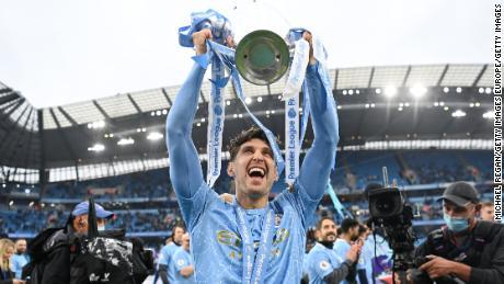 John Stones celebrates with the Premier League trophy.