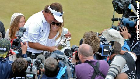 Mickelson holds the Claret Jug with wife Amy after winning the 142nd Open Championship at Muirfield in 2013.