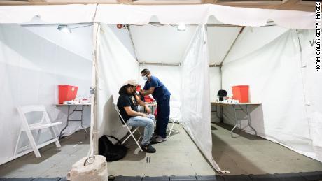 2021 년 5 월 26 일 뉴욕의 Penn Station에서 한 사람이 Covid-19 예방 접종을 받았습니다.