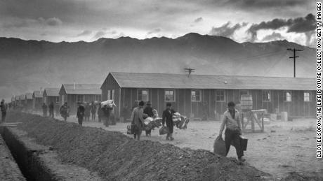 The first group of 82 Japanese-Americans arrive at the Manzanar internment camp (or 'War Relocation Center') carrying their belongings in suitcases and bags in 1942.