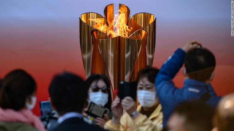 TOPSHOT - People wearing face masks take pictures in front of the Tokyo 2020 Olympic flame, which is displayed outside Sendai railway station, Miyagi prefecture on March 21, 2020, after arriving from Greece. (Photo by Philip FONG / AFP) (Photo by PHILIP FONG/AFP via Getty Images)