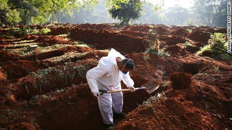 Um trabalhador de cemitério cava sepulturas para os corpos de pessoas que morreram de Covid-19 em São Paulo neste mês.