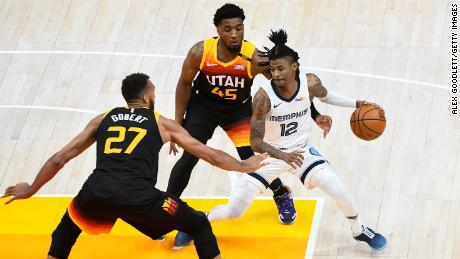 Ja Morant of the Memphis Grizzlies attempts to drive between Donovan Mitchell and Rudy Gobert of the Utah Jazz in Game 2 of the Western Conference first-round playoff series on May 26, 2021.