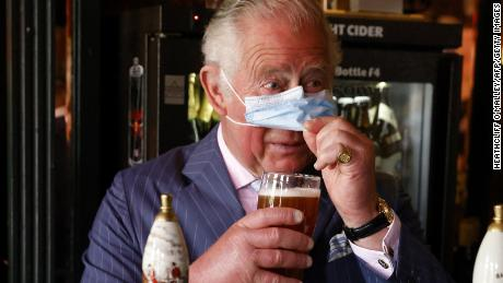The Prince of Wales lifts his face covering to sample a pint he poured during a visit to the Prince of Wales pub in Clapham Old Town, south London on Thursday.