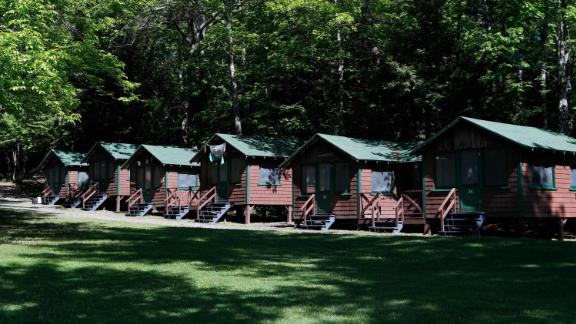 FILE - This Thursday, June 4, 2020 file photo shows a row of cabins at a summer camp in Fayette, Maine. On Friday, May 28, 2021, the Centers for Disease Control and Prevention posted guidance saying kids at summer camps can skip wearing masks outdoors, with some exceptions. Children who aren't fully vaccinated should still wear masks outside when they're in crowds or in sustained close contact with others -- and when they are inside, and fully vaccinated kids need not wear masks indoors or outside, the CDC says. (AP Photo/Robert F. Bukaty, File)