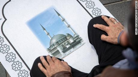 A man participates in Friday prayers outside the Taksim Mosque during the opening ceremony.