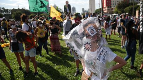 Một người biểu tình đeo biểu ngữ cáo buộc Bolsonaro tội diệt chủng.