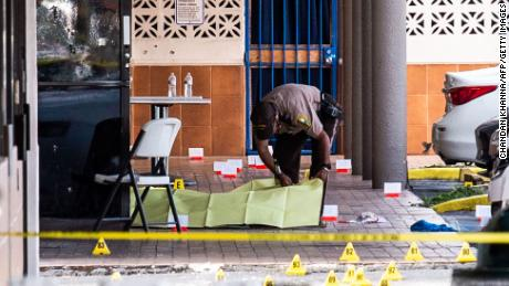 A Miami-Dade police officer covers a dead body after three gunmen killed two people and injured at least 20 people in the Hialeah area of Miami-Dade County in Florida on May 30.