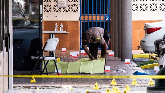 A Miami-Dade officer covers a body outside a club that was rented out for a concert.