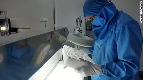 A Borosil worker in a lab wearing personal protective equipment.
