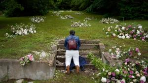"""Linda Porter of Birmingham, Ala., kneels at a makeshift memorial of flowers for the Tulsa Race Massacre at stairs leading to a now empty lot near the historic Greenwood district during centennial commemorations of the massacre, Tuesday, June 1, 2021, in Tulsa, Okla. """"We came to remember,"""" said Porter, who came to Tulsa for the centennial commemorations. (AP Photo/John Locher)"""