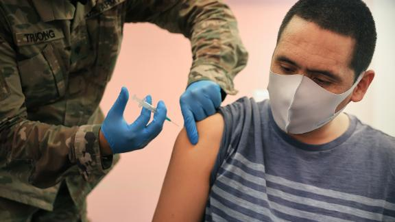 """WHEATON, MARYLAND - MAY 21: Maryland National Guard Specialist James Truong (L) administers a Moderna coronavirus vaccine at CASA de Maryland's Wheaton Welcome Center on May 21, 2021 in Wheaton, Maryland. The mobile vaccination clinic was staffed with members of the Maryland National Guard and part of the Maryland Vaccine Equity Task Force, which works with local health departments and community organizations to focus COVID-19 vaccination efforts on """"underserved, vulnerable, and hard-to-reach populations."""" (Photo by Chip Somodevilla/Getty Images)"""