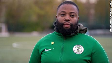 """Grenfell Athletic FC's Head-Coach Rupert Taylor poses for a photograph during a football training session at Paddington Recreational Ground in north London on April 15, 2021. - The Grenfell Athletic team badge is a symbol of what """"a community had and lost"""" when a blaze ripped through a London tower block four years ago, killing scores of residents. Britain's deadliest domestic fire since World War II left 72 people dead, with an official report blaming highly combustible cladding fixed to the 24-storey block as the principal reason the inferno spread. """"The purpose of a dragon, if you look up its history, is protecting precious items or treasures,"""" Grenfell Athletic founder Rupert Taylor told AFP. - TO GO WITH AFP STORY BY Pirate IRWIN (Photo by Niklas HALLE'N / AFP) / TO GO WITH AFP STORY BY Pirate IRWIN (Photo by NIKLAS HALLE'N/AFP via Getty Images)"""