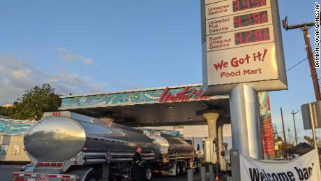 A truck driver checks the gasoline tank level at a United Oil gas station in Sunset Blvd., Los Angeles on May 20.