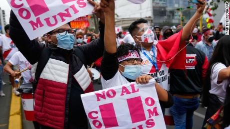 """Fujimori supporters carry signs which read """"No to communism."""""""