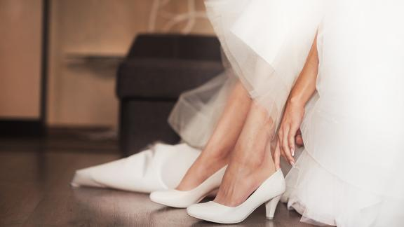 Woman putting on bridal shoes