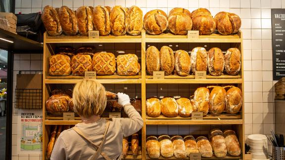 A worker selects a loaf of fresh bread for a customer on a bakery stall inside Danilovsky market in Moscow, Russia, on Wednesday, March 24, 2021.In Russia, food prices in particular have shot up, adding to adecline in living standards during the pandemic. Photographer: Andrey Rudakov/Bloomberg via Getty Images