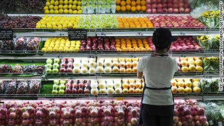 2021 년 6 월 3 일 필리핀 카 비테 주 바쿠 르에있는 SM 시티 바쿠 르 쇼핑 센터에있는 슈퍼마켓의 신선한 농산물 매장에서 판매 보조원이 과일을 준비합니다.