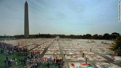 Visitors and volunteers walk on the 21,000-panel AIDS Memorial Quilt on October 10, 1992 in Washington.