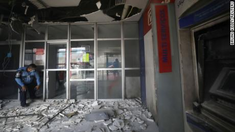 A police officer inspects a Bradesco bank branch damaged in Manaus, Brazil, on June 6, 2021.