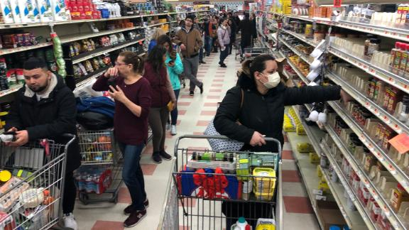 CHELSEA, MA - MARCH 13: A woman in a protective mask shops as a line of shoppers stretch to the back of the store waiting to check-out at the Market Basket in Chelsea, MA on March 13, 2020. People stock up amid coronavirus concerns. (Photo by Bill Greene/The Boston Globe via Getty Images)
