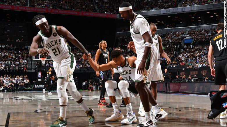 Jrue Holiday dan Bobby Portis dari Bucks membantu Antetokounmpo selama pertandingan mereka melawan Nets